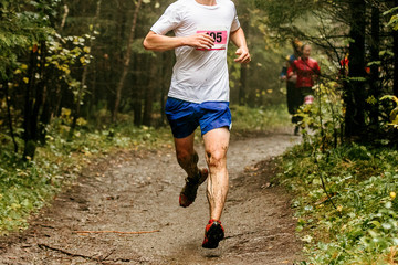 Fototapete - athlete runner with dirty feet running on spring forest trail