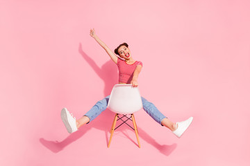 Nice attractive glamorous lovely adorable shine cheerful cheery optimistic girl wearing striped tshirt jeans sitting on chair having fun raising hand up isolated over pink pastel background Wall mural