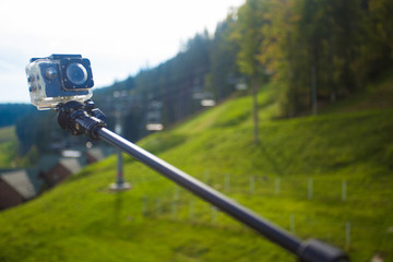action camera on selfie stick on peak of mountains