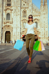 smiling solo tourist woman walking with colorful shopping bags