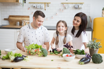 Happy family Mother. father and daughter in preparing healthy vegetables  together  in the kitchen. Help children to parents.