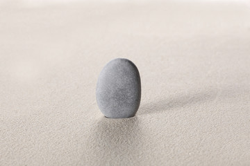 zen stone concept: grey stoneson the sand with copy space for your text