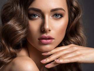 Beautiful woman with brown hair. Beautiful face of an attractive model with fashion makeup.