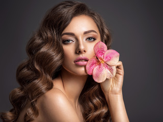 Stunning girl holds flower near eyes. Beautiful woman with brown hair.