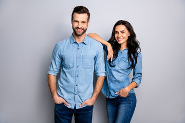 Portrait of charming millennial students workers freelancers entrepreneurs take decisions solutions achieve aims touching shoulders by arms dressed in blue denim outfit on ashy-gray isolated