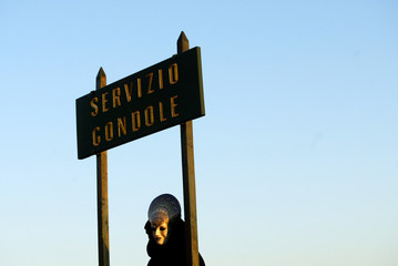 Masked reveller stands near gondolas service sign during traditional Carnival in Venice.
