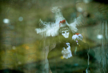 A VENETIAN DRESSED IN A TRADITIONAL OUTFIT IS REFLECTED IN A PUDDLE DURING THE VENICE CARNIVAL.