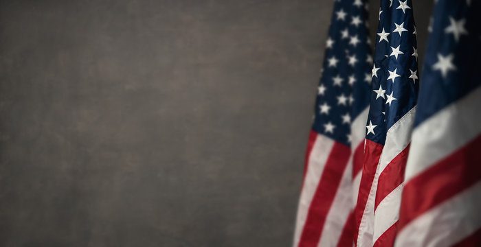 American flags over gray wall, 4th of july panoramic background with copy space