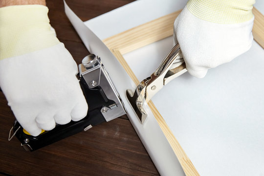 Wrapping canvas on wooden stretcher bar. Staple gun, canvas pliers, male hand in white protect gloves