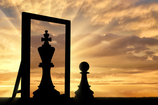 Silhouette of a pawn, sees himself in the reflection of the mirror queen.