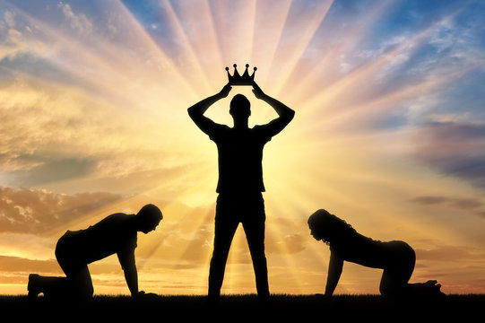 Silhouette of a woman and a man worshiping a man who puts a crown on his head against the sunset