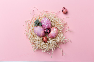 Colorful Easter eggs in nest on pink background. Easter texture