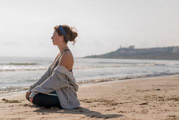 chica meditando en la orilla del mar