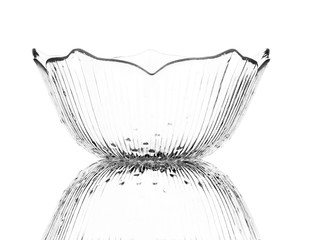 A single empty glass dessert bowl isolated on a white background with reflection. High contrast black and white, black line lighting.
