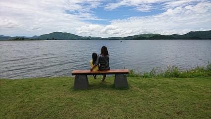 Une mère regarde le lac calme avec sa fille dans les bras