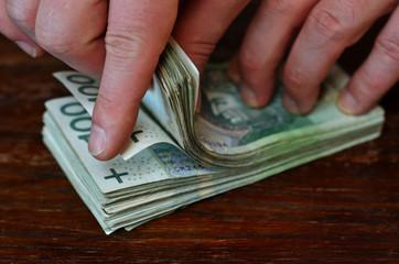 A man counting Polish 100 zlotys