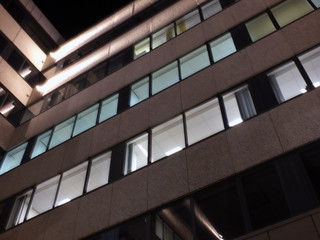 the corner of an office building at night with illuminated walls and lights shining on the exterior facade