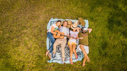 Top vertical aerial view of group of friends lay down on the meadow and enjoy the friendship playing a guitar and relaxing all together - people  friends in outdoor leisure activity