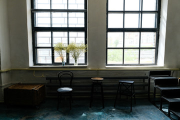 View of an empty room with different antique chairs large panoramic window against a white brick wall. Stylish loft interior of the Studio.
