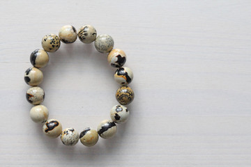 Bracelet from a natural landscape jasper. Bracelet made of natural stones on a white background. Jewelry made of natural stones. Copy space for your text