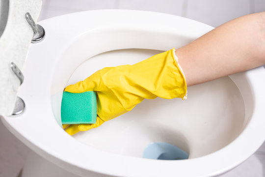 Close-up of hands  cleaning toilet