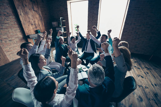 Above high angle view of nice stylish cheerful glad positive sharks marketers company ceo boss chief executive directors raising hands up motivation day at industrial loft interior work place space