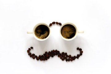 Human face with glasses from two espresso cups and mustache from coffee beans. Coffee art or creative concept. Top view