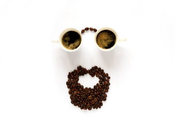 Human face with glasses from two espresso cups and beard from coffee beans. Coffee art or creative concept. Top view