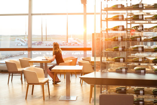 Woman waiting in the cafe in airport terminal and looking at window at airplane