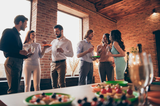 Company of six nice trendy attractive pretty elegant cheerful glad positive caucasian guys ladies pairs pal having fun luncheon brunch best tradition table buffet snack in industrial loft interior
