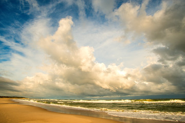 lonesome beach of the Baltic Sea with cloudy sky and surf