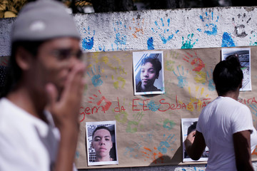 Students cry in front of pictures of the victims shooting at the Raul Brasil school during a tribute in Suzano