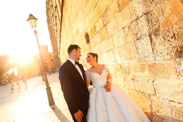 Beautiful wedding couple posing in sun at streets