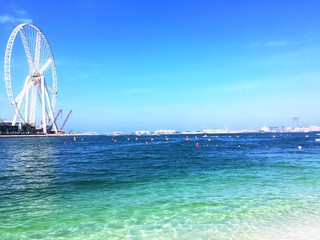 The Dubai eye under construction and the blue waves in the sunny day
