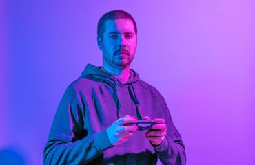 Purple light portrait of a man holding a mobile