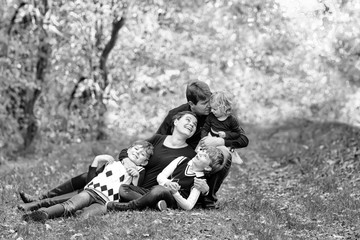 Portrait of young parents with three children. Mother, father, two kids brothers boys and little cute toddler sister girl having fun together in autumn forest. Happy family of five