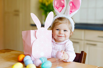 Cute little toddler girl wearing Easter bunny ears playing with colored pastel eggs. Happy baby child unpacking gifts. Adorable kid in pink clothes enjoying holiday