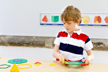 Little kid boy playing with lots of colorful plastic blocks kit in school or preschool nursery. Happy child having fun with building and creating geometric figures, learning mathematics and geometry.