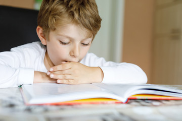Little blonde school kid boy reading a book at home. Child interested in reading magazine for kids. Leisure for kids, building skills and education concept