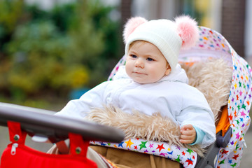 Cute little beautiful baby girl sitting in the pram or stroller on autumn day. Happy healthy child going for a walk on fresh air in warm clothes. Baby with in colorful clothes and hat with bobbles