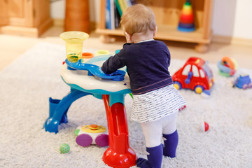 Adorable cute beautiful little baby girl playing with educational sorter toys at home or nursery. Healthy happy toddler child learning sorting colors and forms