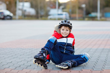 Little school kid boy skating with rollers in the city. child in protection safety clothes. Active schoolboy making sports and learning to skate on inline skater. Falling down and getting hurt