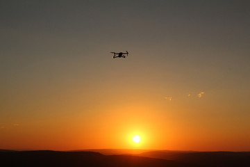Modern technology showing a silhouetted drone flying against an orange sunset background.