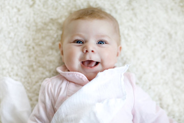 Close-up of a two or three months old baby girl with blue eyes. Newborn child, little adorable peaceful and attentive girl looking surprised at the camera. Family, new life, childhood concept.