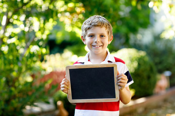 Happy little kid boy with chalk desk in hands. Healthy adorable child outdoors Empty desk for copyspace holding by beautiful schoolkid