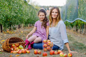 Portrait of little girl and beautiful mother with red apples in organic orchard. Happy woman and kid daughter picking ripe fruits from trees and having fun. Harvest season for family.