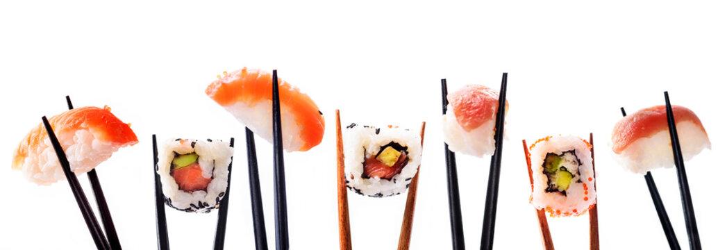 Creative sushi rolls on bamboo chopstick isolated on white background. Japanese luxury cuisine menu.
