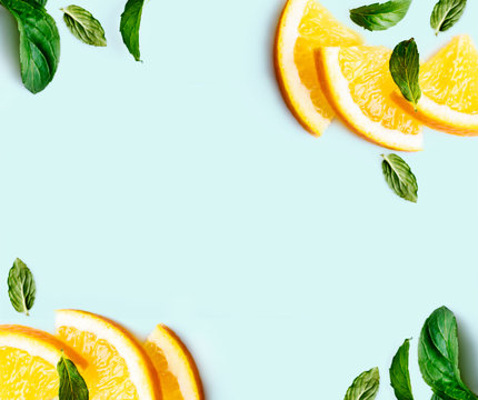 Citrus slices and mint herbs frame on retro mint pastel background with copyspace from above. Top view of lemon and orange refreshment.