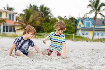 Two little kids boys having fun on tropical beach, happy best friends playing, friendship concept. Siblings brothers, twins in family look with palms on background. Family vacations on Florida.