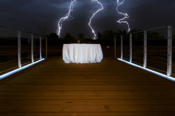 outdoor elegant white table on a wooden bridge at night with a thunderstorm and lightings